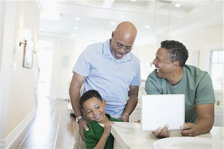 Happy mature man holding digital tablet while standing with father and son at counter Stock Photo - Premium Royalty-Free, Code: 613-07848353