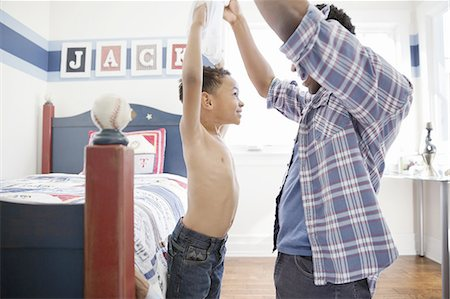 Father removing son's shirt in bedroom Stock Photo - Premium Royalty-Free, Code: 613-07848374