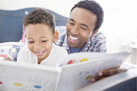 story - Happy father and son reading book together in bed Stock Photo - Premium Royalty-Free, Code: 613-07848376