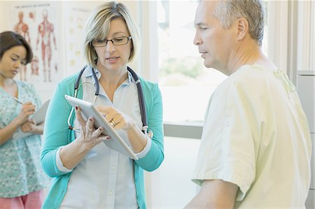 Female doctor explaining reports on digital tablet to patient with nurse writing notes in background Stock Photo - Premium Royalty-Free, Code: 613-07848442