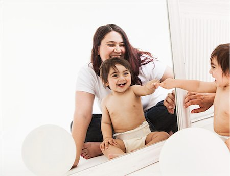 Mother and baby smiling at reflection in mirror Stock Photo - Premium Royalty-Free, Code: 613-07848646