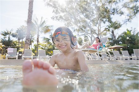father son shirtless - Smiling boy sitting in pool with parents in background Stock Photo - Premium Royalty-Free, Code: 613-07848883