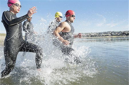 Triathletes running into water Stock Photo - Premium Royalty-Free, Code: 613-07848939