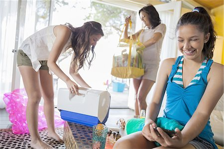 Teen girl using smartphone while sister and mother pack for beach Stock Photo - Premium Royalty-Free, Code: 613-07848975