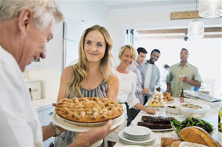 Group of friends and family at kitchen island for a dinner party Stock Photo - Premium Royalty-Free, Code: 613-07849170