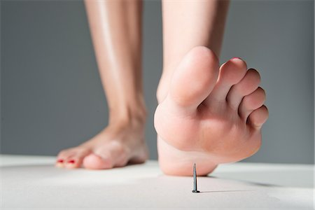female feet close up - Foot about to step on nail Stock Photo - Premium Royalty-Free, Code: 613-07849220