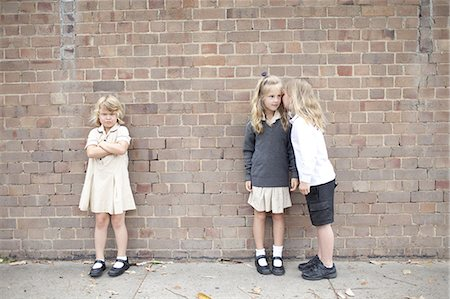 school girl uniforms - Bullying and whispering in school playground Stock Photo - Premium Royalty-Free, Code: 613-07849352