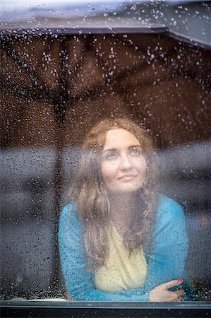 Woman inside looking at the rain on a window Stock Photo - Premium Royalty-Free, Code: 613-08056947