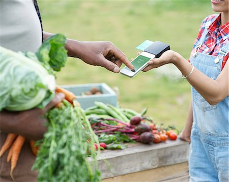farm phone - Man paying for vegetables. Stock Photo - Premium Royalty-Free, Code: 613-08057412