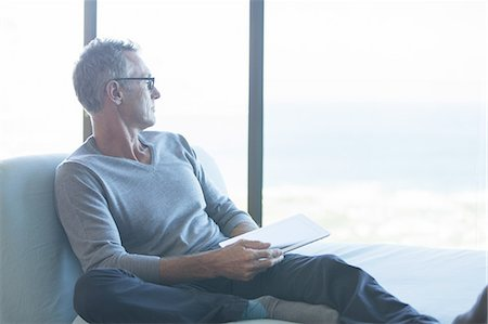 Man sitting by window with digital tablet Stock Photo - Premium Royalty-Free, Code: 613-08201664