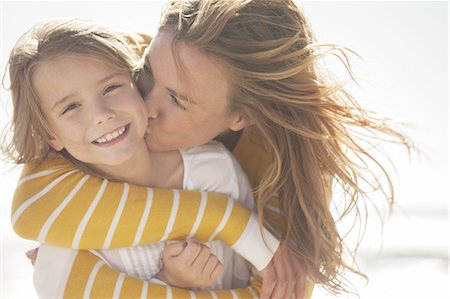 Close up of mother kissing daughter at beach Stock Photo - Premium Royalty-Free, Code: 613-08242464