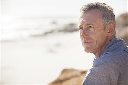 portrait looking away - Close up of mature man relaxing on beach Stock Photo - Premium Royalty-Free, Code: 613-08242489