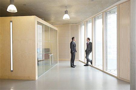 Businessmen talking in office hallway Stock Photo - Premium Royalty-Free, Code: 613-08242703