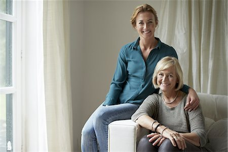 Confident mother and daughter sitting on sofa Stock Photo - Premium Royalty-Free, Code: 613-08387725