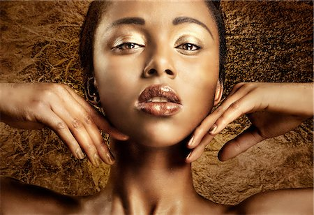 Portrait of a woman with bronze and gold makeup Stock Photo - Premium Royalty-Free, Code: 613-08391072