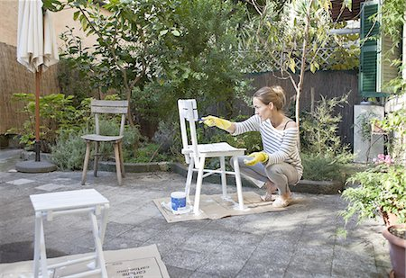 south european - woman painting wooden chairs in garden Stock Photo - Premium Royalty-Free, Code: 613-08391469