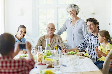 Boy photographing family at dining table Stock Photo - Premium Royalty-Free, Code: 613-08391799