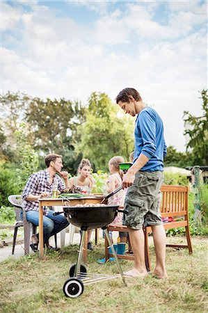 Family At Barbeque In Garden Stock Photo - Premium Royalty-Free, Code: 613-08391869