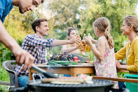 Family At Barbeque Event In Backyard Stock Photo - Premium Royalty-Free, Code: 613-08391861