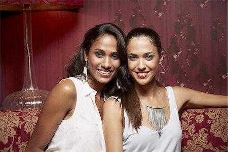 Glamorous friends sitting on sofa in nightclub Stock Photo - Premium Royalty-Free, Code: 613-08544409