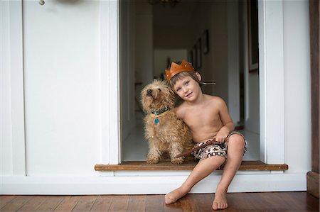 Young boy at home cuddling dog, sword, kings crown Stock Photo - Premium Royalty-Free, Code: 613-08633507