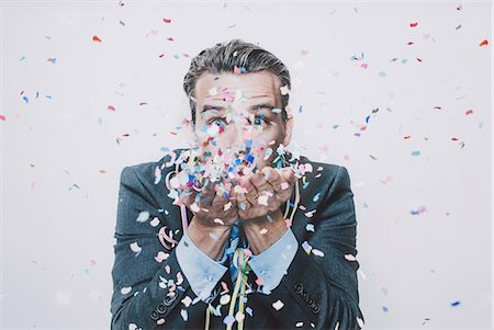 Business man blowing confetti. Stock Photo - Premium Royalty-Free, Code: 613-08654600
