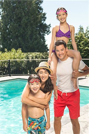 Smiling family standing by swimming pool Stock Photo - Premium Royalty-Free, Code: 613-08654648