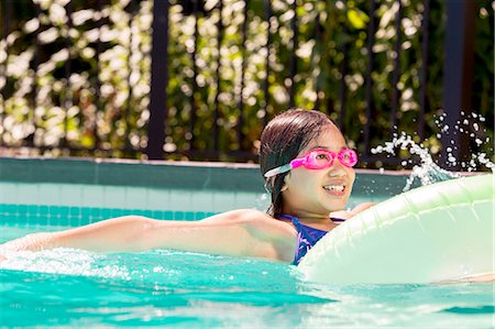 preteen swim - Smiling girl floating in inner tube in pool Stock Photo - Premium Royalty-Free, Code: 613-08654643