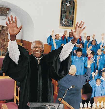 Priest Standing on a Pulpit With His Arms Upraised in Front of a Gospel Singing Choir Stock Photo - Premium Royalty-Free, Code: 613-00455851