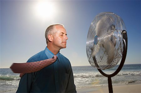 sweaty businessman - Hot, Relieved Businessman With His Eyes Closed Standing Next to an Electric Fan on a Beach Stock Photo - Premium Royalty-Free, Code: 613-00632568