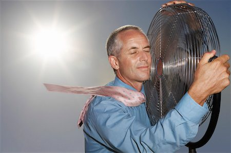 sweaty businessman - Hot, Relieved Businessman Holding an Electric Fan Stock Photo - Premium Royalty-Free, Code: 613-00632569