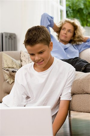 Boy (13-15) using laptop, mother relaxing on sofa in background Stock Photo - Premium Royalty-Free, Code: 613-00702400