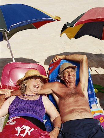 seniors woman in swimsuit - Senior couple lying on sun beds on beach, smiling Stock Photo - Premium Royalty-Free, Code: 613-00703015
