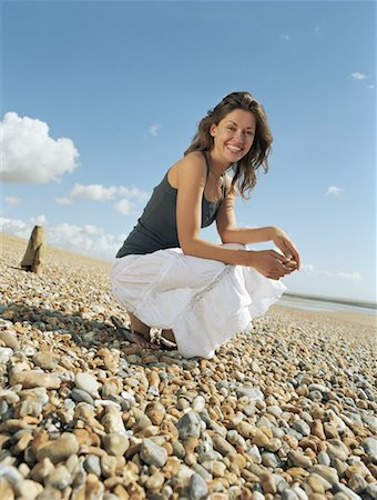 Young woman crouching on pebble beach, smiling, portrait Stock Photo - Premium Royalty-Free, Code: 613-00810639