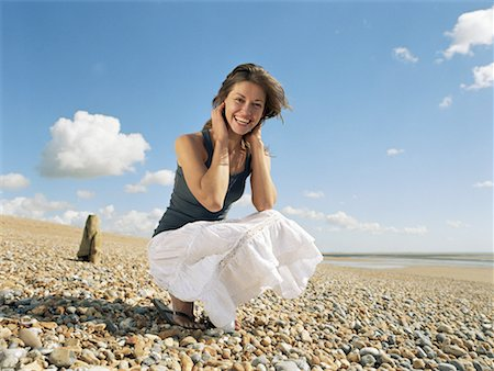 Young woman crouching on beach, smoothing hair and smiling, portrait Stock Photo - Premium Royalty-Free, Code: 613-00811142