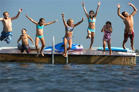 Group of children (5-12) leaping off landing platform into sea Stock Photo - Premium Royalty-Free, Code: 613-00812751