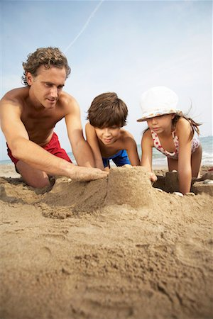 Father building sandcastles with son and daughter (7-9) Stock Photo - Premium Royalty-Free, Code: 613-00834427