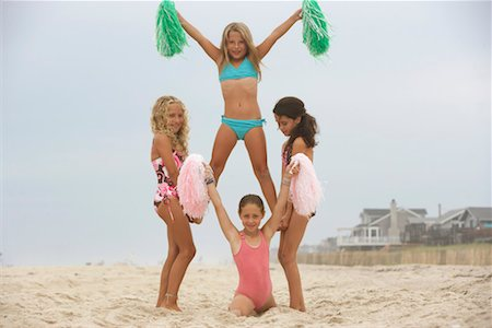 Four girls (8-12) practicing cheerleading formation on beach, portrait Stock Photo - Premium Royalty-Free, Code: 613-00862890