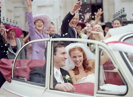 family image and confetti - Bride and groom in convertible car, wedding party waving in background Stock Photo - Premium Royalty-Free, Code: 613-00863455