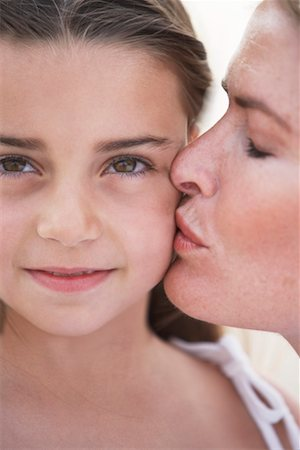 daughter kissing mother - Mother kissing daughter (6-8) on cheek, close-up Stock Photo - Premium Royalty-Free, Code: 613-00863787