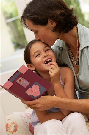 daughter kissing mother - Mother kissing daughter (5-7), woman holding card Stock Photo - Premium Royalty-Free, Code: 613-00908119
