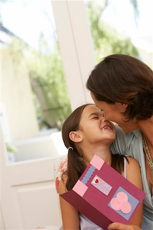 daughter kissing mother - Mother embracing daughter (5-7), woman holding card Stock Photo - Premium Royalty-Free, Code: 613-00909462