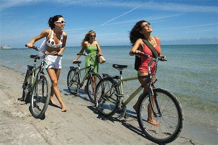 Three young women walking bicycles along beach, smiling Stock Photo - Premium Royalty-Free, Code: 613-00998457