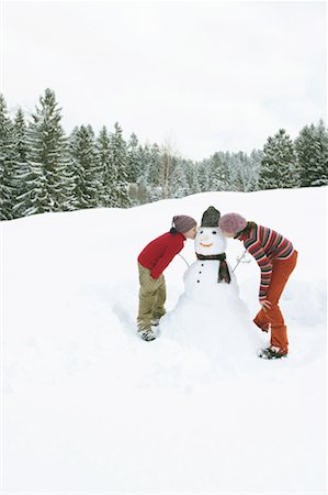 Brother and sister (9-13) bending over kissing snowman, side view Stock Photo - Premium Royalty-Free, Code: 613-00998685