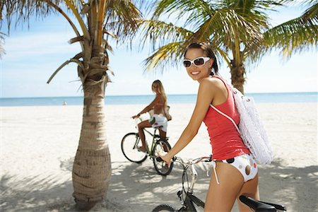 Two young women on bicycles on beach, portrait (focus on foreground) Stock Photo - Premium Royalty-Free, Code: 613-00998686
