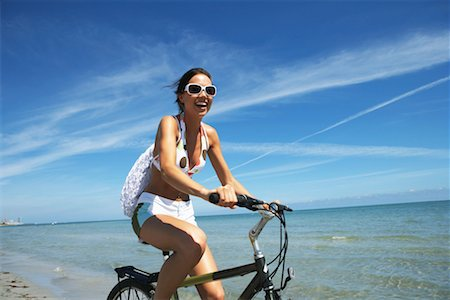 Young woman riding bicycle on beach, smiling, portrait, close- up Stock Photo - Premium Royalty-Free, Code: 613-00999108