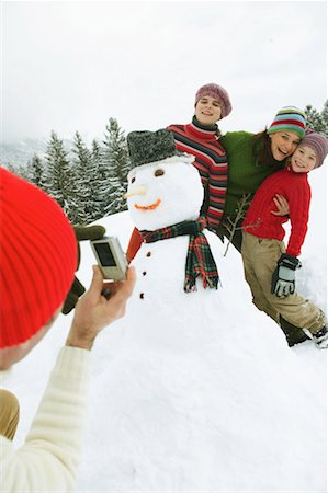 Man taking picture of family by snowman with digital camera Stock Photo - Premium Royalty-Free, Code: 613-00999231