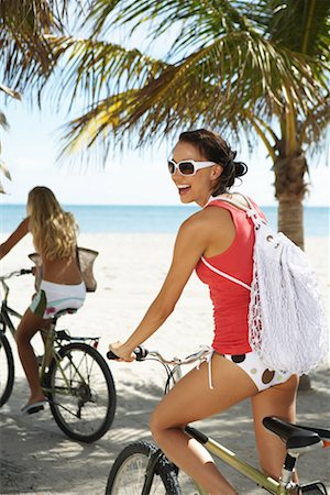 Two young women on bicycles on beach, close-up (focus on foreground) Stock Photo - Premium Royalty-Free, Code: 613-00999263