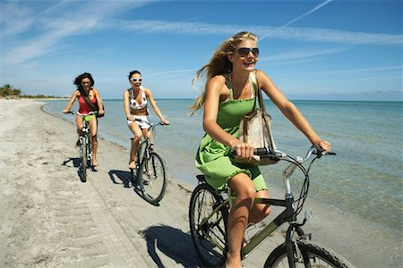 Three young women riding bicycles on beach, smiling Stock Photo - Premium Royalty-Free, Code: 613-00999389