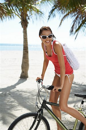 Young woman smiling on bicycle, close-up Stock Photo - Premium Royalty-Free, Code: 613-00999443